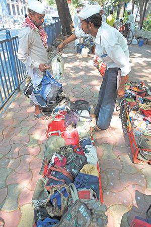 Die Boten sortieren die Taschen und Tiffin-Boxen auf dem Fußweg.
