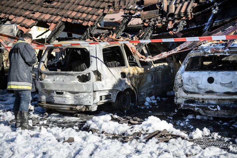 Ein Brandermittler am 20. November inmitten des Löschschaums bei der Arbeit, nachdem das Carport mit drei Autos in Kundl brannte.