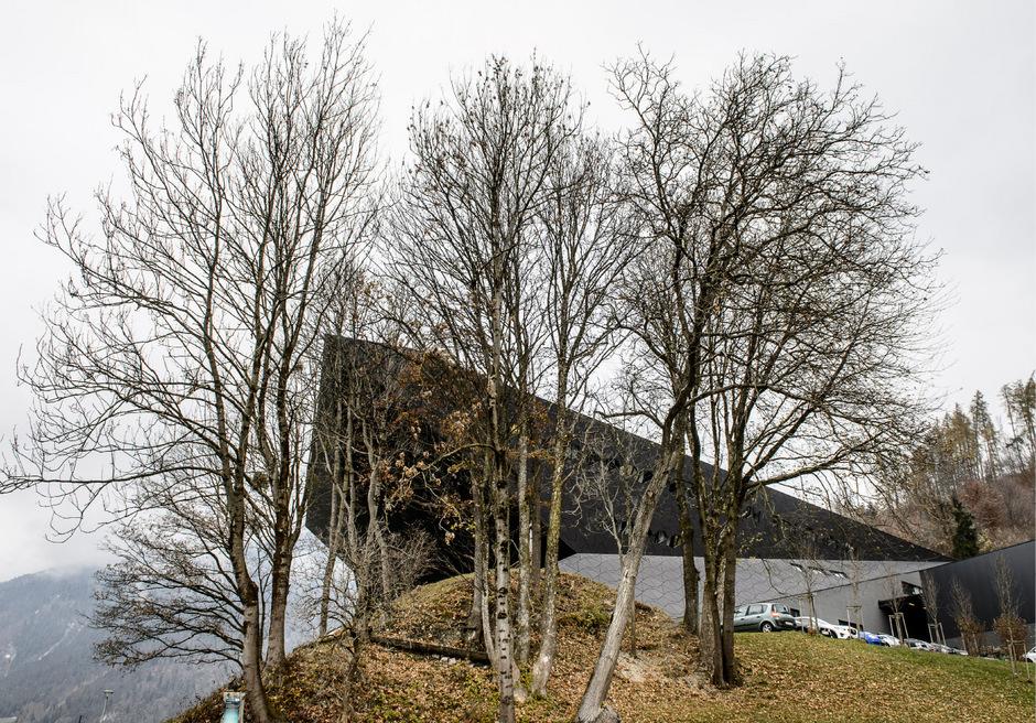 Das Erler Festspielhaus zwischen den winterlich kahl gewordenen Bäumen.