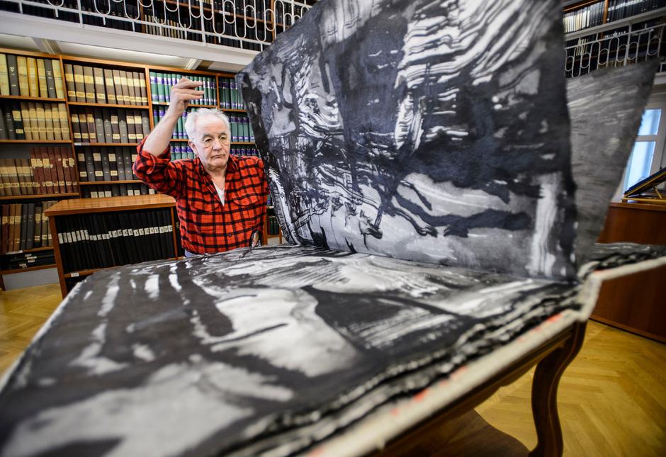 """Turi Werkner beim Blättern in einem seiner großformatigen Kunstbücher. Die darin enthaltenen Werke nennen sich """"Der karierte Regenbogen""""."""