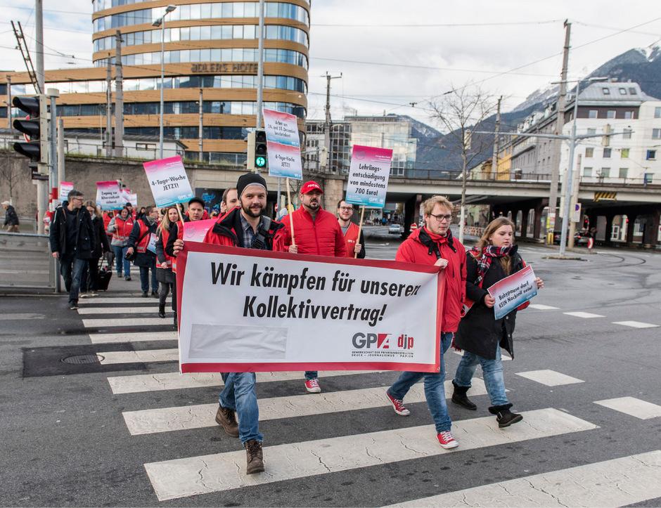 Gewerkschafter mit Transparenten auf dem Weg zum Innsbrucker Sillpark.