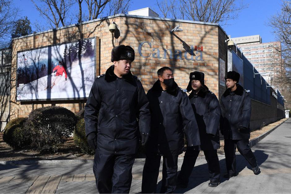 Chinesische Polizisten patrouillieren vor der kanadischen Botschaft in Peking.