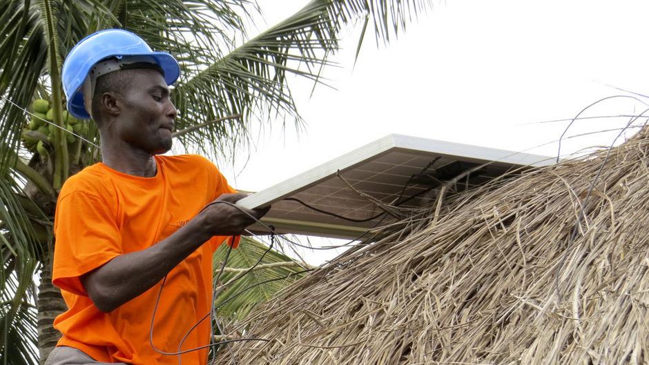 Solarpanele der österreichischen Energy Globe Foundation werden auf einem Schilfdach in Ghana montiert. Insgesamt liegt Österreich bei der Entwicklungshilfe weit unter dem Soll.