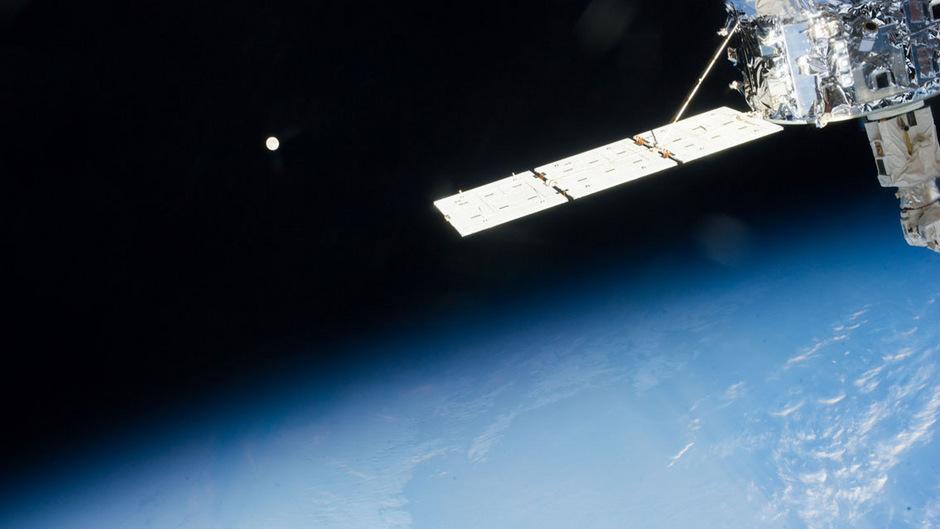 """Der Mond über der Erde, fotografiert im Rahmen der """"Expedition 37"""", rechts im Bild der Raumfahrttransport """"Albert Einstein""""."""
