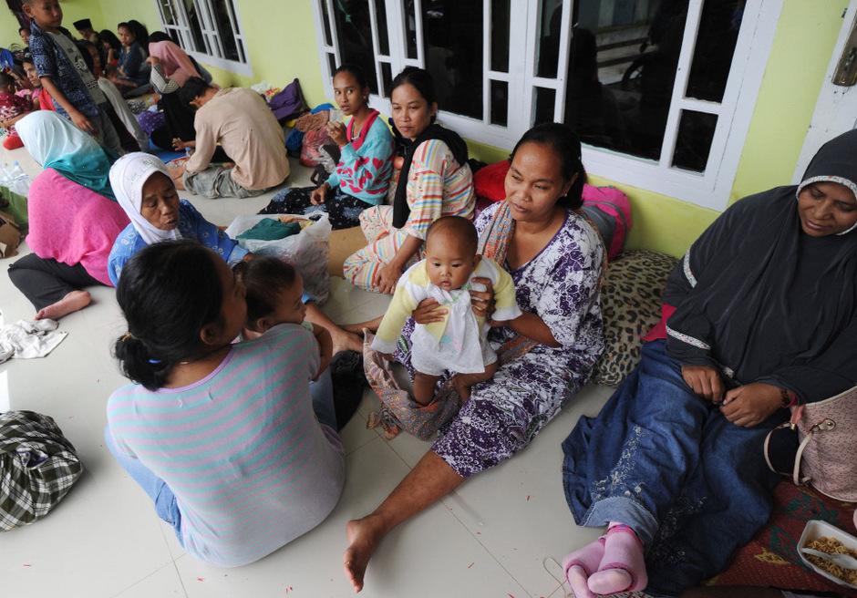 Menschen warten in Java vor den Häusern im Freien.
