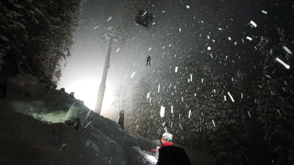 Die Bergretter seilten sich aus der Gondel zu dem verirrten Skifahrer ab.