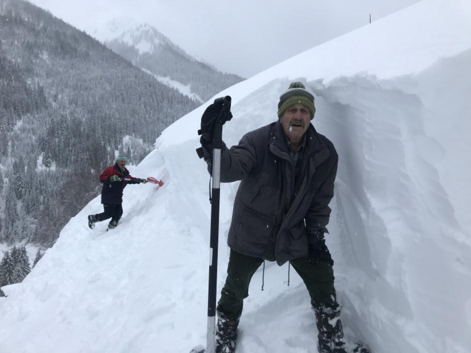 Peter Hosp (l.) und Hubert Amann mühen sich, in Mitteregg ein Dach von der Schneelast zu befreien.