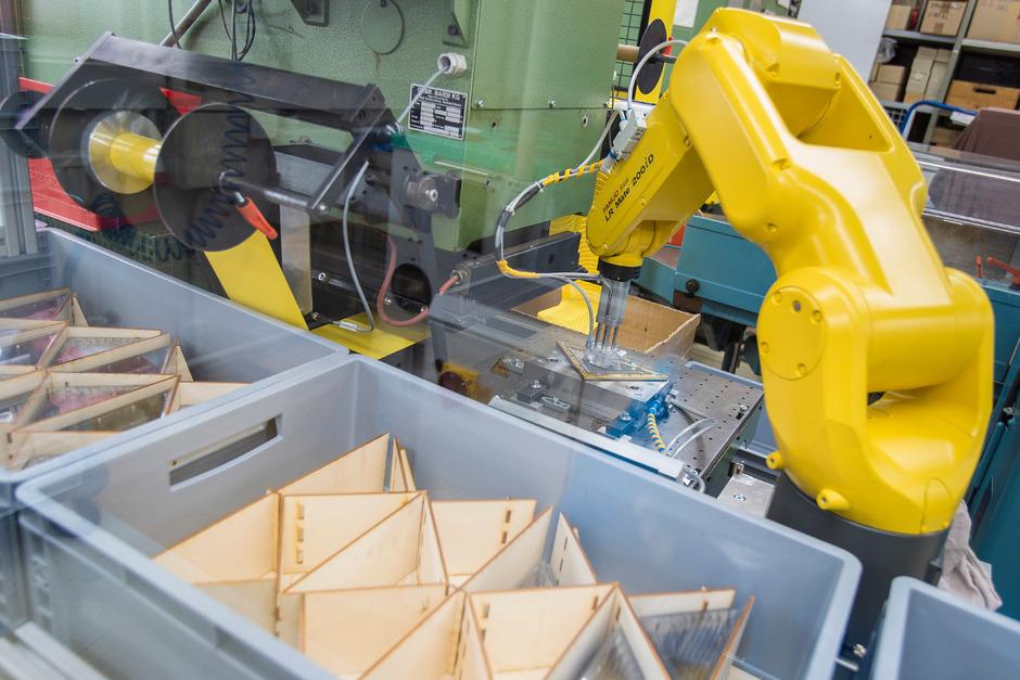 Ein Roboterarm prägt die Aufschrift in das Dreieck.