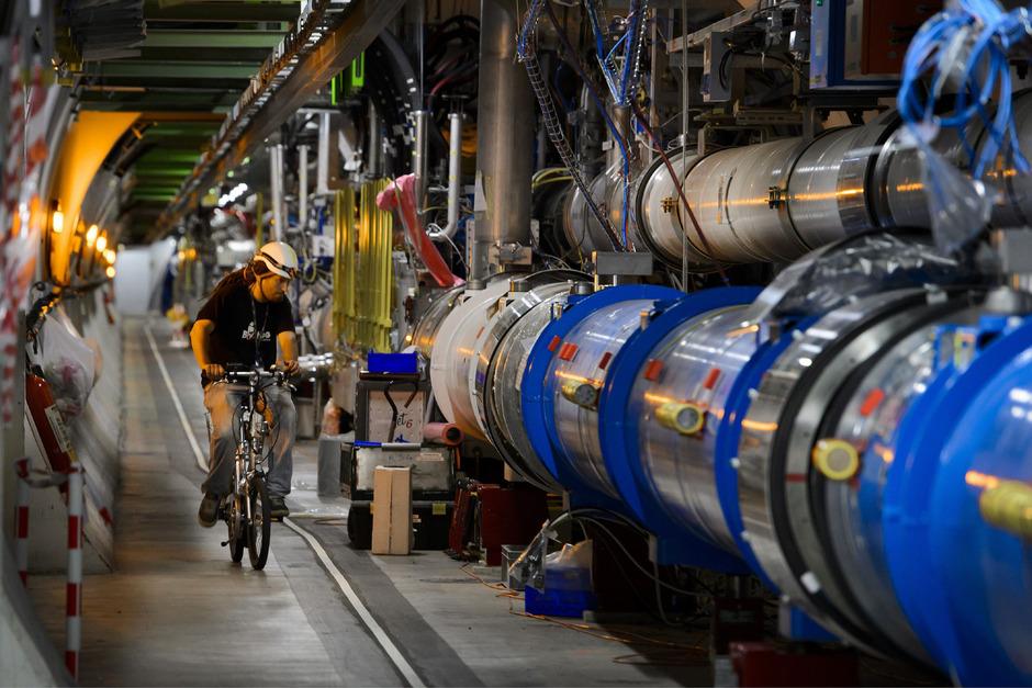 Ein Arbeiter fährt an einer Röhre des Large Hadron Collider (LHC) im CERN entlang.