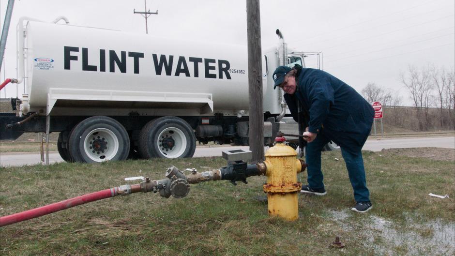 Doku-Aktionismus: Filmemacher Michael Moore flutet den Vorgarten von Gouverneur Rick Snyder mit toxischem Trinkwasser.
