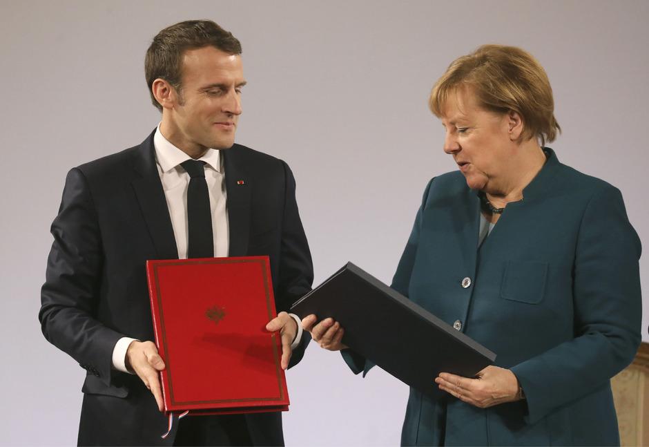 Stolz wie einst aufs Schulzeugnis: Angela Merkel und Emmanuel Macron mit den soeben unterzeichneten Freundschaftsverträgen.