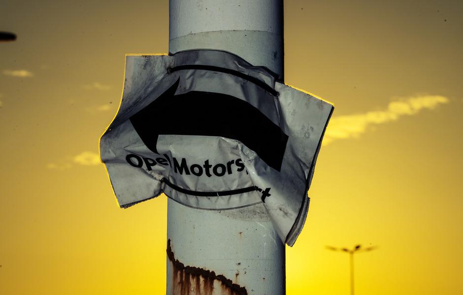 Ein zerknitterter Wegweiser hängt an einem Lichtmast auf dem Opel-Gelände in Rüsselsheim.