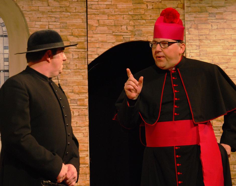 Auf der Bühne: Der Bischof (Hermann Glettler) ermahnt Don Camillo (Markus Narr) mit erhobenem Finger, auf den Einsatz seiner Fäuste zu verzichten.