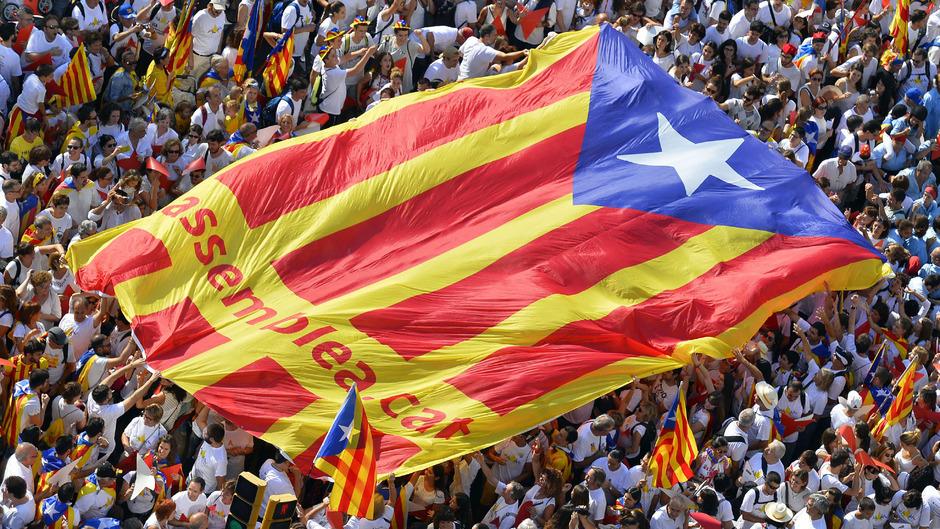 Demonstranten mit einer Estelada, der katalanischen Unabhängigkeitsfahne.