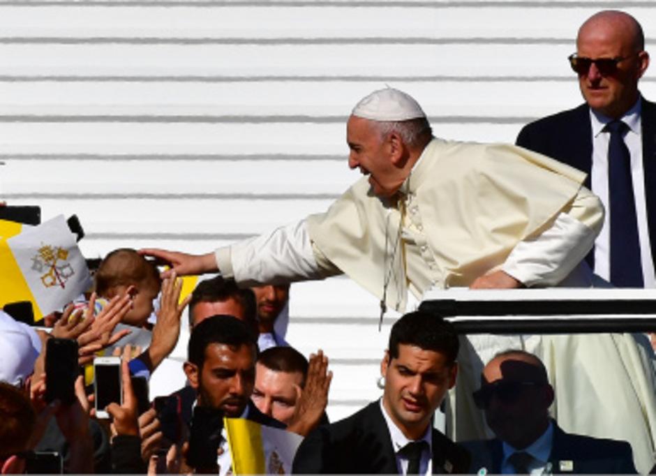 Papst Franziskus segnet ein Kind während er mit dem Papamobil durch die Menge gefahren wird.