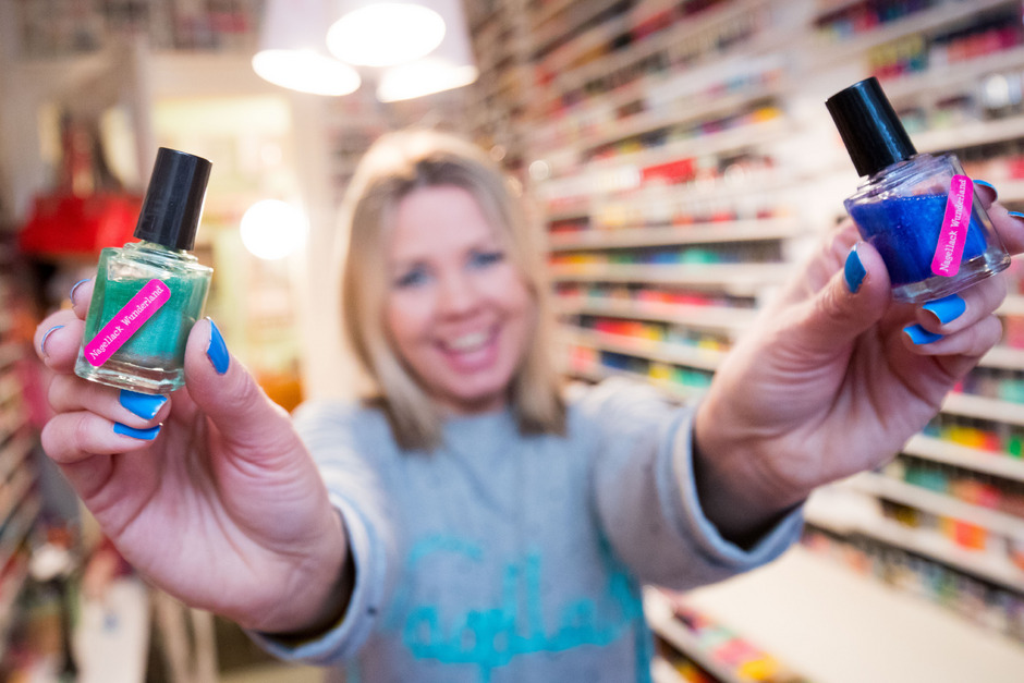 Carolin Gorra zeigt zwei Fläschchen mit selbstentworfenem Nagellack in einem Zimmer mit Teilen ihrer Nagellacksammlung.