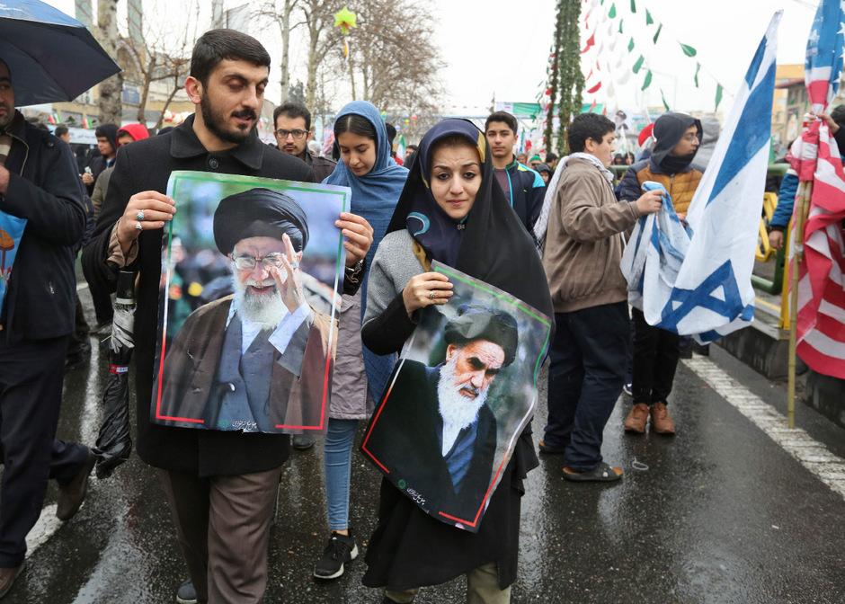 Feiern zum Jahrestag der Islamischen Revolution im Iran. Unterstützer mit dem Foto des Obersten Führers Ali Khamenei und Ayatollah Ruhollah Khomeini (r.).