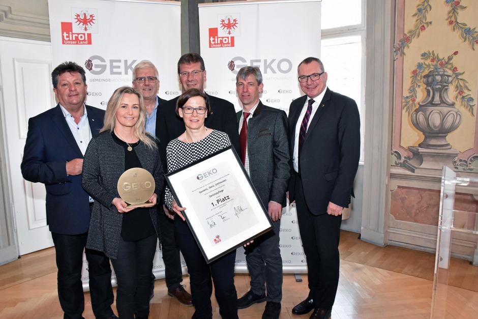 Gemeindeverbandspräsident Ernst Schöpf, BM Manfred Köll, BM Jakob Wolf, BM Hansjörg Falkner und LR Johannes Tratter (v.l.) feierten mit Sandra Friedl und Patrizia Pichler (v.l., Oetztalpflege) die Auszeichnung.
