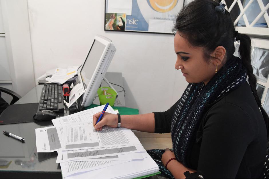 """Eine Frau in Rom beim Ausfüllen des Formulars für die """"Reddito di cittadinanza""""."""