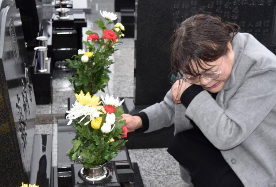Eine Frau trauert am achten Jahrestag der Katatstrophe von Fukushima um einen Angehörigen.