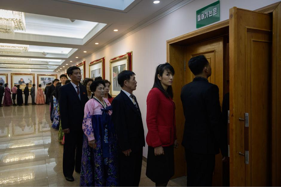 Wähler stehen vor der Wahlkabine Schlange.