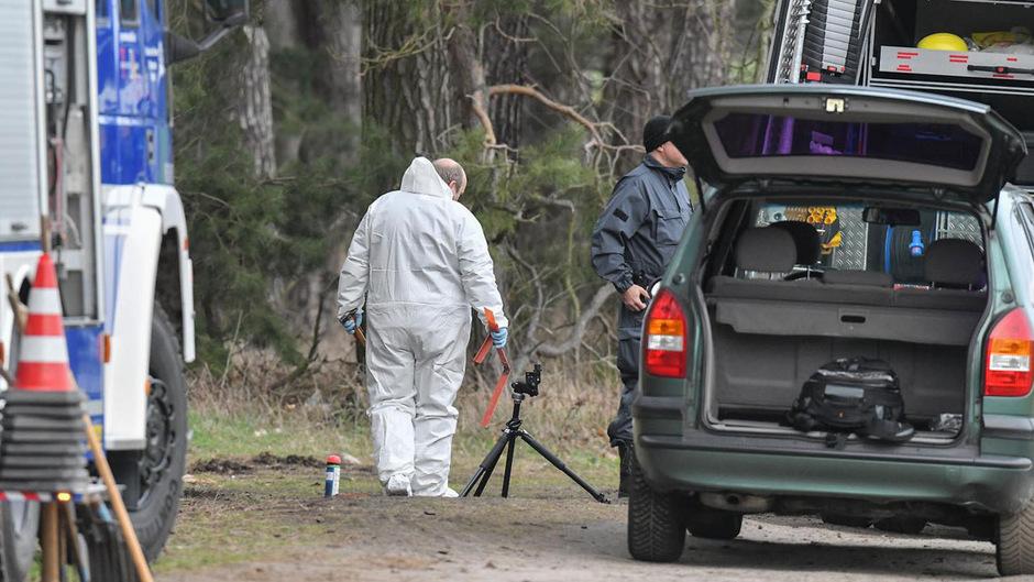 Kriminaltechniker sichern Spuren auf dem Boden an einem Waldgebiet im Landkreis Oder-Spree.