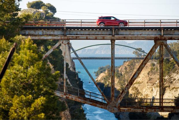 Auf einer Eisenbahnbrücke überquert der neue Range Rover Evoque den Kanal von Korinth.