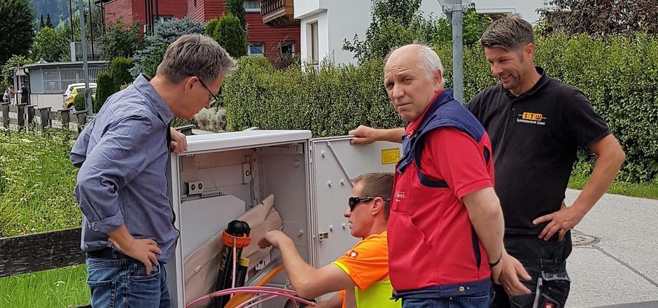 Der Heinfelser Bürgermeister Georg Hofmann (l.) mit den Arbeitern der Firma, die einen Verteilerkasten für Glasfaser vorbereiten.