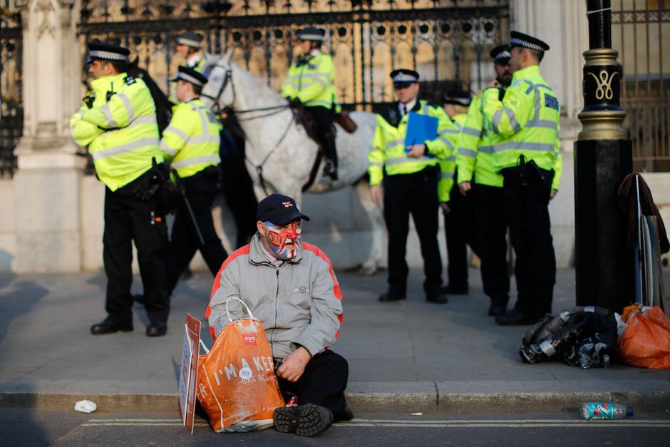 Ein Pro-Brexit-Aktivist vor dem Parlament, das von Polizisten bewacht wird.