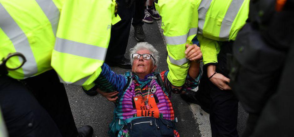 Eine Aktivistin wird von Polizisten weggetragen.