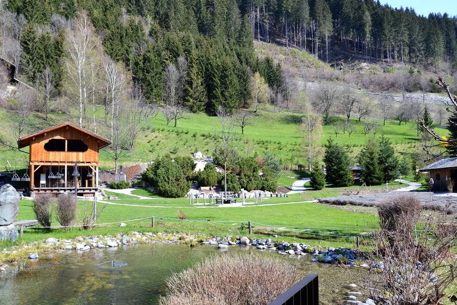 Zu den acht Sinnesstationen des Vitalpinums gehören die Brennerei in der Holzhütte und der Kräutergarten (rechts im Bild).
