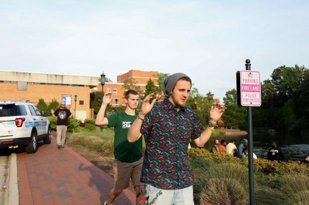 Mit erhobeben Händen versließen die Studenten das Uni-Gelände.