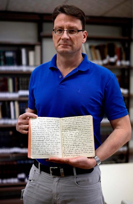 Archivar Stefan Litt mit dem Tagebuch des jüdischen Schriftstellers Moshe Yaakov Ben-Gavriel.