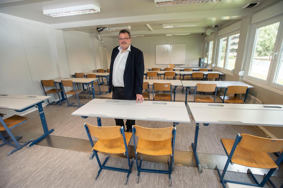 Direktor Harald Pittl im Container-Ausweichquartier. Diese Stühle und Tische müssen auch mit in das neue Schulgebäude. Nun sucht man nach Lösungen.