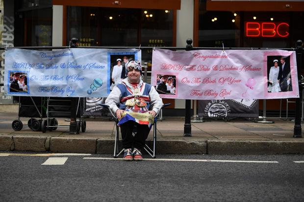 Dieser Royal-Fan campiert bereits seit Tagen in Windsor und hält Glückwunsch-Plakate in Blau und Rosa parat.