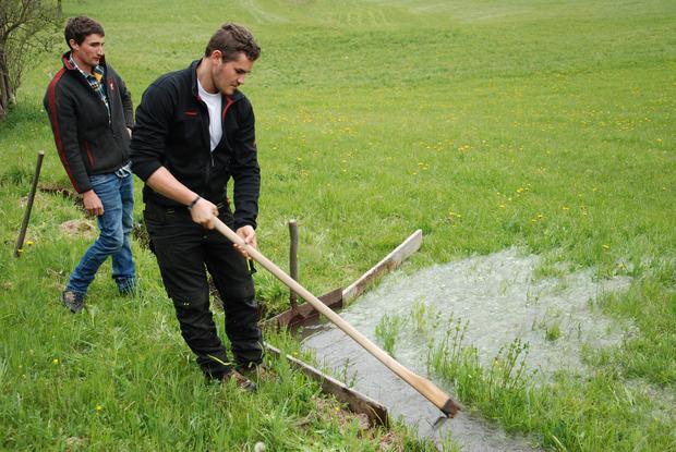 Mathias (l.) und Lukas Schöpf aktivieren die Rieselbewässerung in Ried.