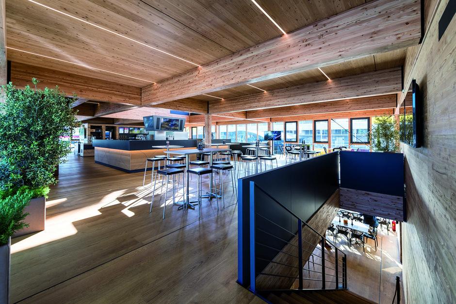 """Zwischen Lack, Plastik und Glas sticht die neue """"Energy Station"""" von Red Bull mit dem Baustoff Holz heraus."""