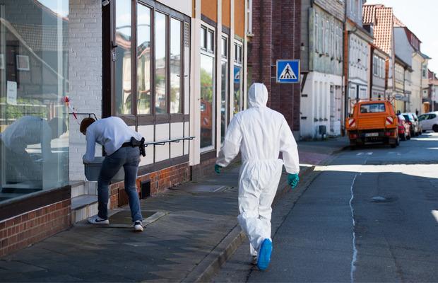 Ein Polizist und ein Mitarbeiter der Spurensicherung beim Tatort in Wittingen.