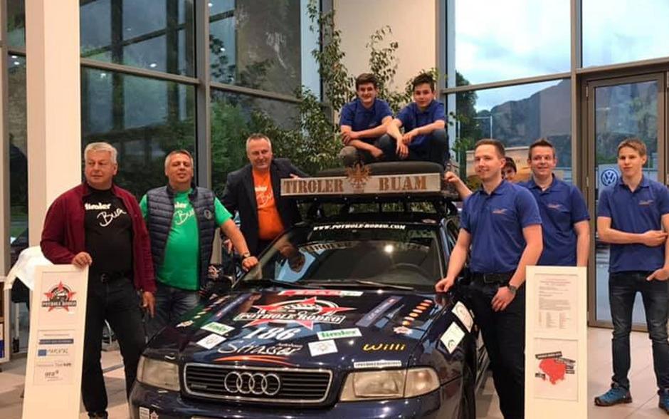 Kurt und Jakob Scheidnagl sowie Martin Reiter (v.l.) mit den Mechaniker-Lehrlingen, die das 20 Jahre alte Auto auf die abenteuerliche Reise vorbereitet haben.