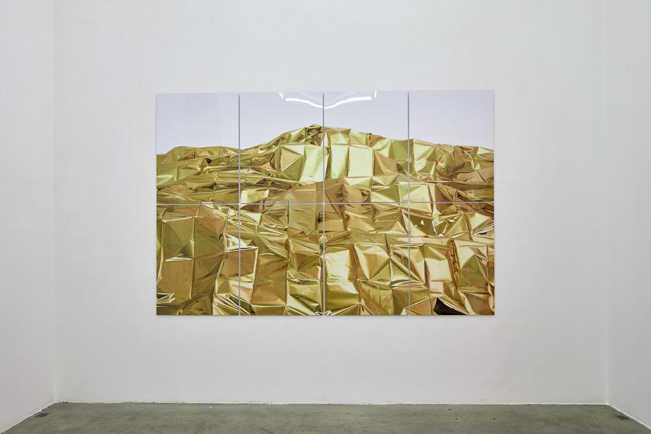 Eine von Nikolaus Schletterer aus goldfarbenen Rettungsdecken konstruierte fiktive Berglandschaft.