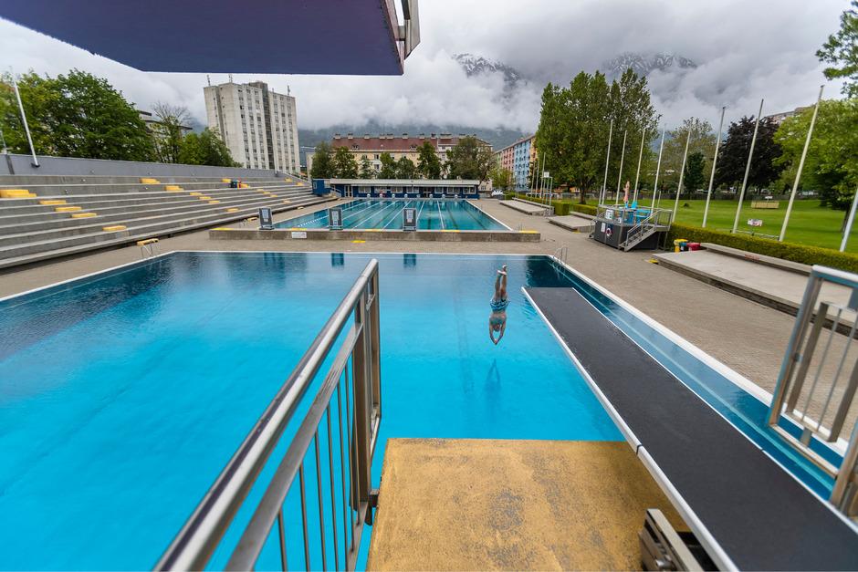 Im Innsbrucker Tivoli-Bad will dieser Tage nicht so recht Badestimmung aufkommen. Vereinzelte Mutige springen dennoch ins Wasser.