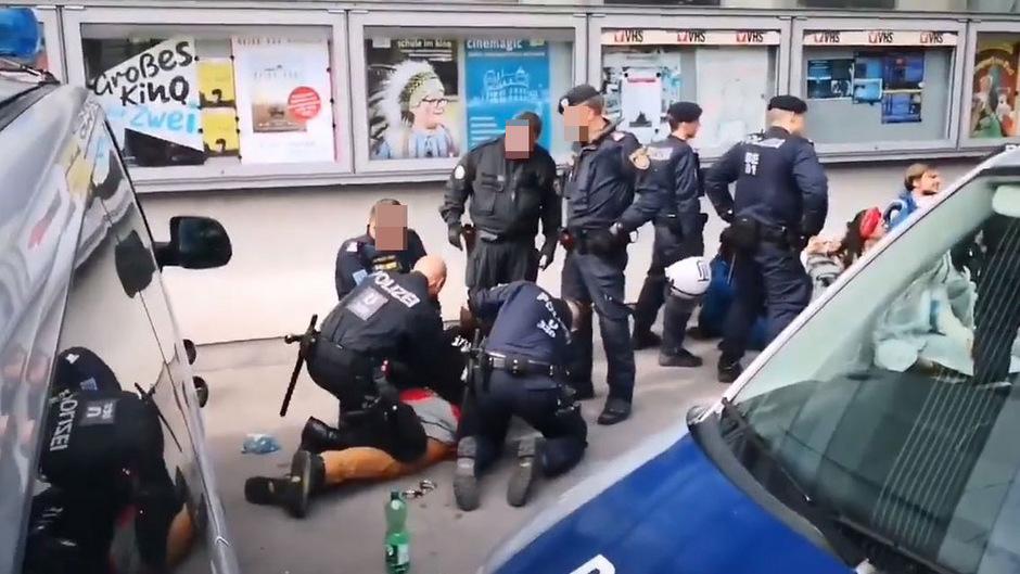 Nachdem der Mann bereits wehrlos am Boden zu sein scheint, versetzt ihm noch ein Beamter Faustschläge.