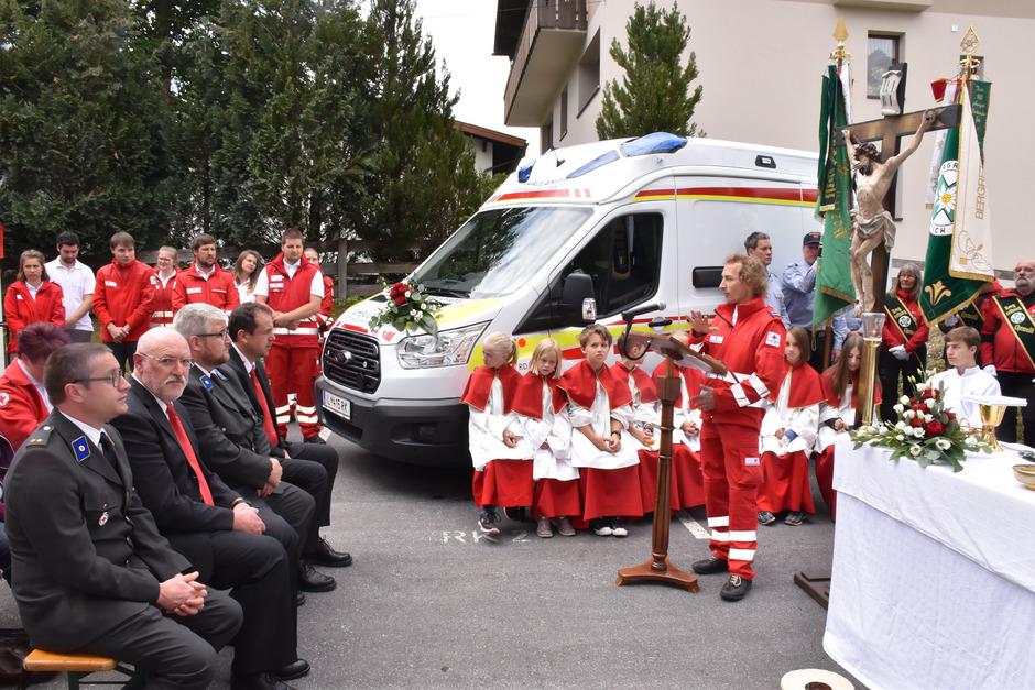 Nach Messe und Segnung hält Rotkreuz-Ortsstellenleiter Tobias Mitterbauer vor dem neuen Einsatzfahrzeug eine kurze Willkommensrede.