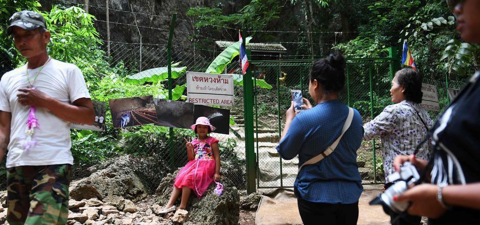 Vor dem gesperrten Eingang zur Höhle posiert ein junges Mädchen.