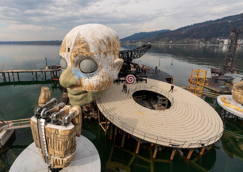 Dominiert wird die Bühne der Bregenzer Festspiele für Giuseppe Verdis Oper, die 2019 zum ersten Mal überhaupt auf der Seebühne gespielt wird, von einem knapp 14 Meter hohen Kopf und zwei ebenso überdimensionalen Händen.