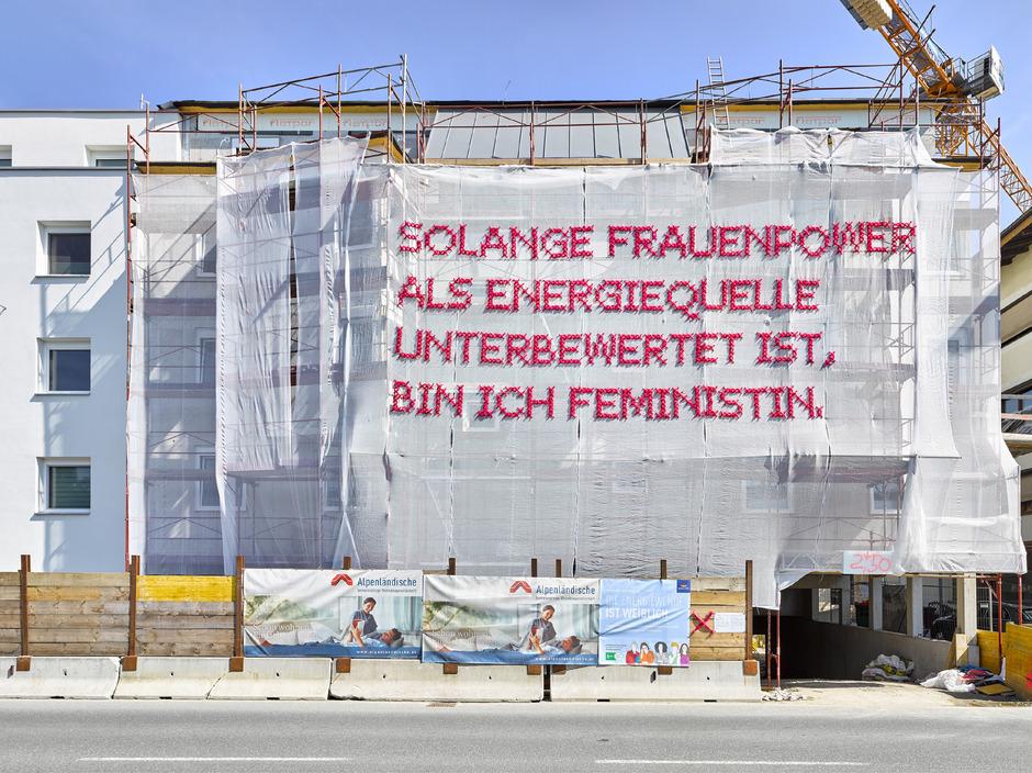 Das gesellschaftskritische Kunstwerk ist an der Nordfassade der Baustelle am Wörgler Fischerfeld zu sehen.