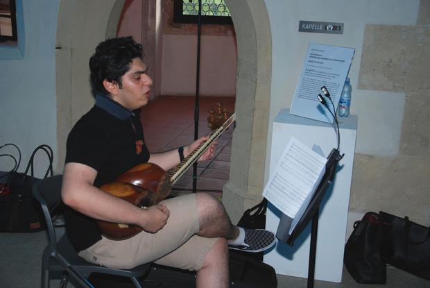 Danial Moazeni spielt auf dem persischen Saiteninstrument Tar.
