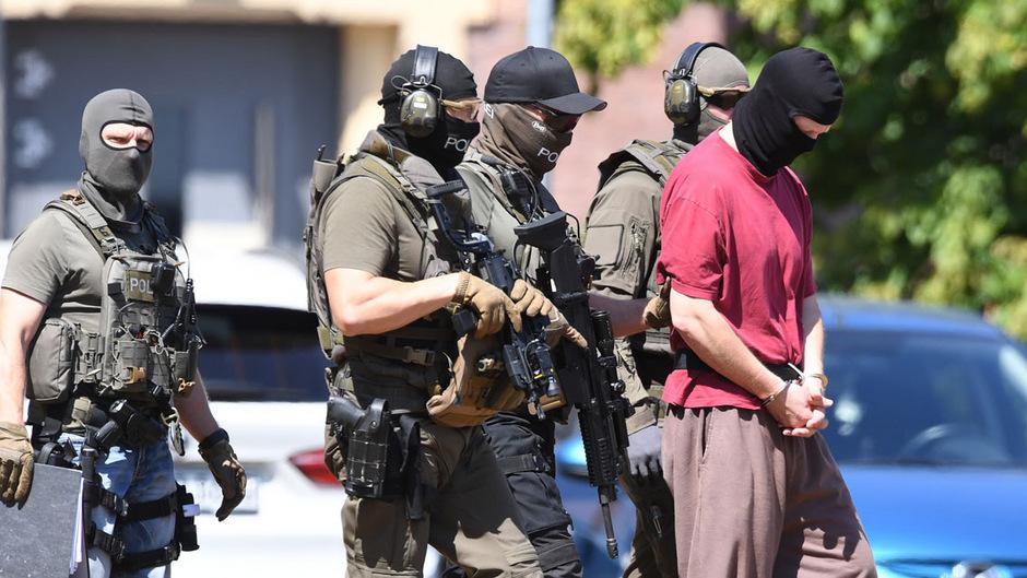 Der Tatverdächtige Stephan E. umkreist von Polizisten.