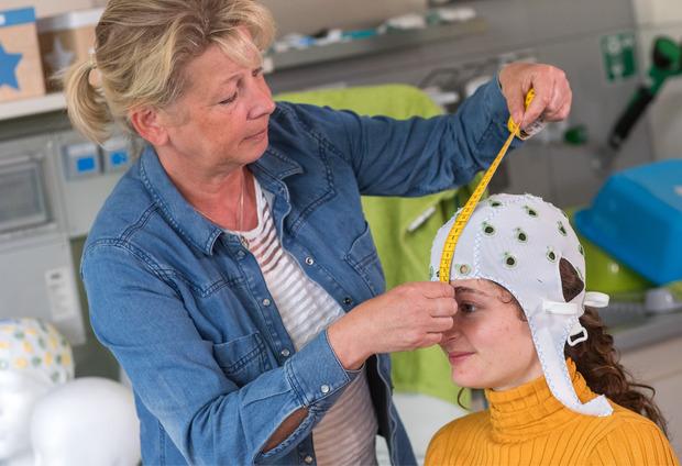 Die medizintechnische Assistentin Gabi Schöns richtet eine Haube mit Elektroden zur Messung der Hirnströme im Labor für Neurobiologie am Leibniz-Institut bei einer Probandin ein.