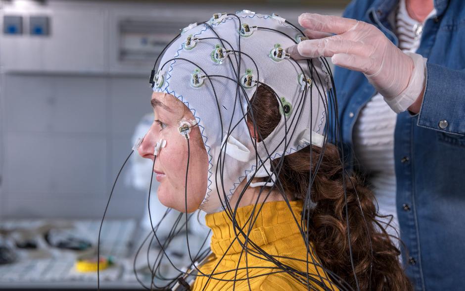 Eine Messmethode setzt bei den elektrischen Strömen im Gehirn an. Dafür bekommen die Probanden Hauben mit Elektroden für ein EEG auf den Kopf gezogen.